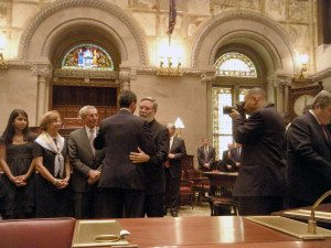 Tomas Gomide embraces then newly-sworn in Senator Jack Martins at his inauguration after he led the senate chamber in prayer.  (Photo by Rich Forestano)