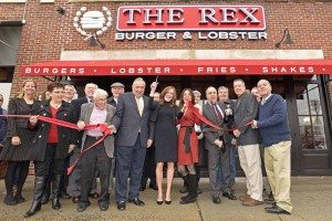 Members of the Mineola Chamber of Commerce, village board and local officials welcome The Rex to Mineola during their ribbon cutting.
