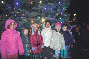 Friends gather around the illuminated tree at Village Green.